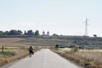 Un hombre anda por una carretera en los alrededores de la localidad vallisoletana de Mucientes.