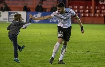 Eneko Undabarrena saluda a un pequeño hincha del Burgos CF tras la victoria de los blanquinegros en Calahorra.