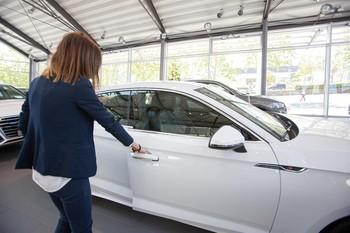 Una mujer abre un coche aparcado en el interior de uno de los concesionarios reabiertos en la Fase 1 de desescalada.
