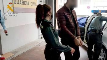 Una agente de la Guardia Civil traslada a uno de los detenidos.