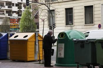 Un hombre deposita vidrio en el contenedor verde en el centro de Logroño.