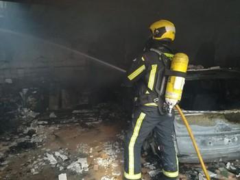 Un bombero apaga las llamas en la vivienda siniestrada