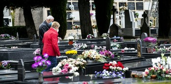 Una pareja deposita unos centros de flores sobre la tumba de sus familiares. Crisantemos, claveles, gladiolos, margaritas, rosas y lillium cubren la mayoría de las lápidas de mármol.