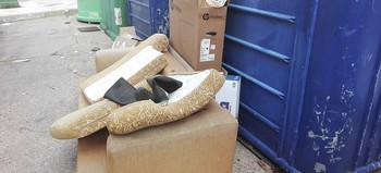 Un sofá junto a los contenedores de cartón