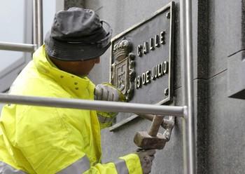 Un operario trabaja en la sustitución de la placa de la calle 19 de Julio, en el centro de Oviedo