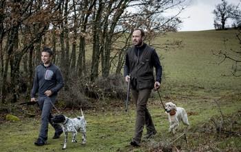 Dos cazadores con sus perros en una imagen de archivo