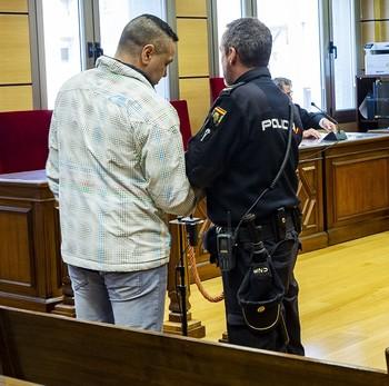 'El Algarrobo', en pie, mientras un policía nacional le quita las esposas antes de ratificar el acuerdo de conformidad delante del Tribunal de la Sección Segunda de la Audiencia Provincial