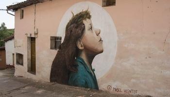 Un mural en la fachada de un casa de pueblo.