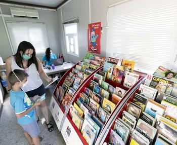 Una mujer y un niño buscan una lectura apetecible en la bibliopiscina.