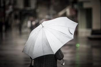 Un ciudadano se protege con un paraguas.