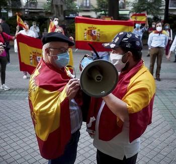 Varias personas protestan en la calle Sarasatse, cerca de la sede del PSOE en Pamplona