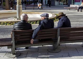Tres hombres conversan sentados en un banco.