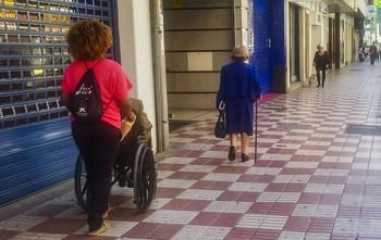 Un cuidador ayuda a un anciano.