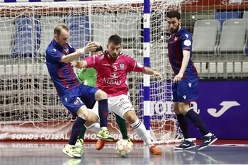 Catela, entre dos jugadores del Levante en las semifinales del play off por el título.