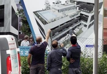 Un grupo de ciudadanos observan el anuncio de una promoción de viviendas en Logroño.