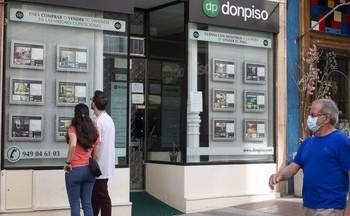 Una pareja se interesa por los pisos en venta ante el escaparate de una inmobiliaria.
