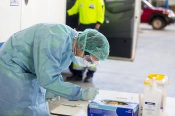 Imagen de archivo de un enfermero mientras recoge una muestra de una prueba de Covid.