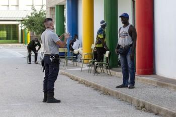 Un temporero conversa con un guardia de seguridad en uno de los pabellones donde han sido reubicados.