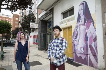 Rachel Merino y Diego Alonso, ayer junto a la pintura que han dedicado a la hija de los Reyes Católicos en la calle María Amigo.