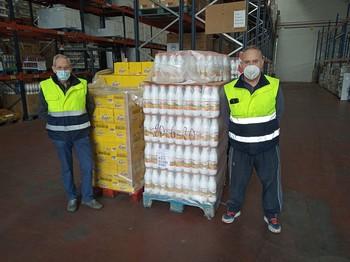 Dos voluntarios del Banco de Alimentos, junto a unos palés con productos de alimentación.
