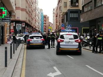 El herido, tendido sobre la acera (en la zona izquierda de la imagen), con agentes de Policía en espera de la llegada de la ambulancia.