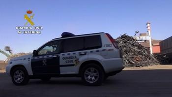 Un coche patrulla pasa frente a un montón de armas dispuestas para entrar en fundición.