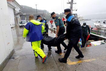 Efectivos de la Policía y la Guardia Civil trasladan a tierra el cuerpo de una de las víctimas.