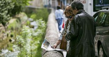 Una pareja de turistas observan un mapa antes de seguir su recorrido.