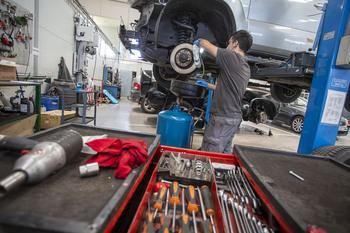 Un mecánico realiza labores de mantenimiento a un vehículo en el taller.