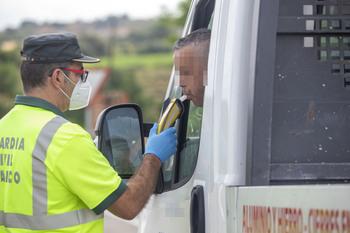 Un conductor se somete a una prueba de alcohol que le sujeta un guardia civil de tráfico.