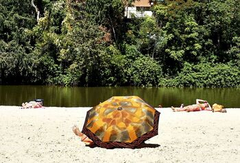 Varias personas toman el sol en la playa de las Moreras en la capital vallisoletana, uno de los espacios autorizados para el baño en la Comunidad.