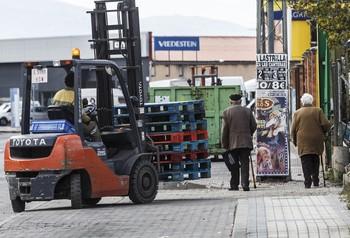 Un trabajador transporta palés en el Polígono Industrial de El Cerro.