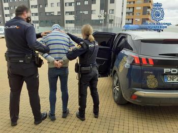 Dos agentes trasladan al detenido.