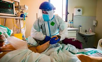 Un sanitario totalmente protegido coge la mano de un paciente ingresado en UCI.
