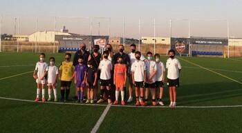 Los organizadores posan con distintos jóvenes futbolistas.