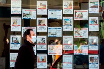 Una persona pasa junto a un cartel de ofertas de viviendas.