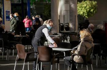 Una camarera desinfecta la mesa de la terraza de un bar a una clienta.
