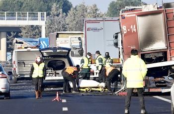 Varios operarios meten los cadáveres a coche fúnebre tras su levantamiento sobre las diez de la mañana.
