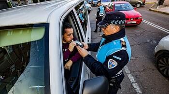 Un agente realiza un test de alcoholemia a un conductor.