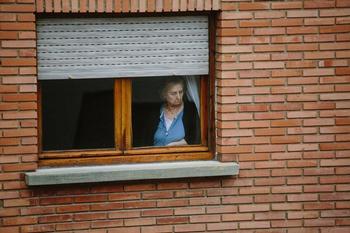 Una mujer observa la calle durante el confinamiento del año pasado.