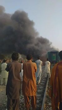 Men look at a burning train after a gas canister passengers were using to cook breakfast exploded, near the town of Rahim Yar Khan