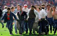 FILE PHOTO: A fan is taken from the pitch after being injured